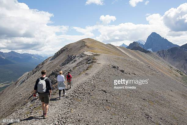 Family walk along path on ridge crest, mtns