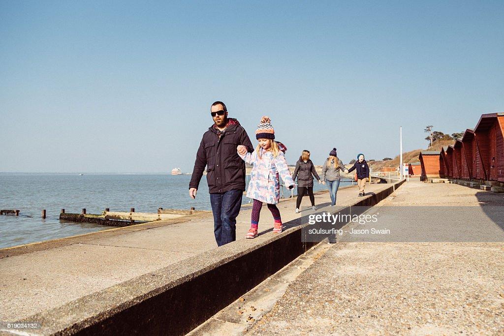 Family walk along the coast : Stock Photo