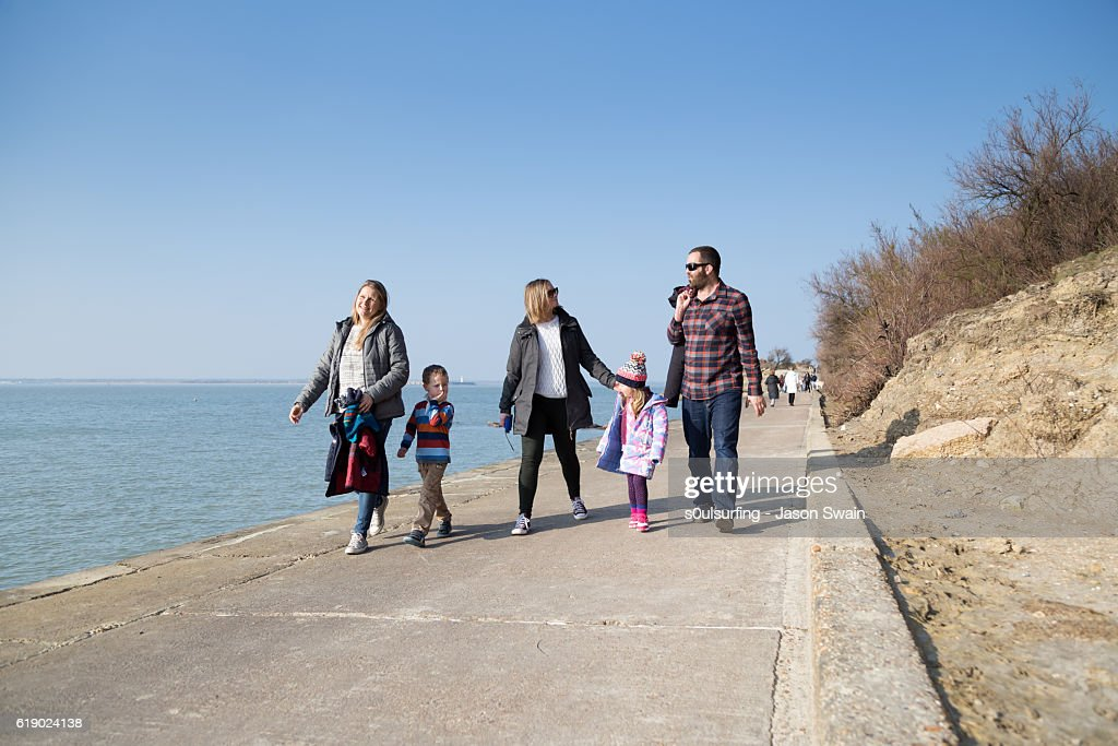 Family walk along the coast : Stock Photo