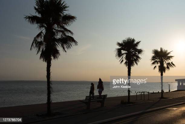 A family walk along the sea front as the sun goes down during the recent warm weather on September 20 2020 in Southend on Sea London