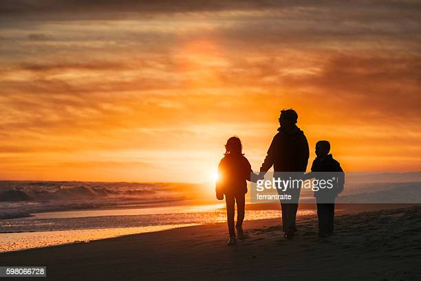 Family walk by the beach at sunset