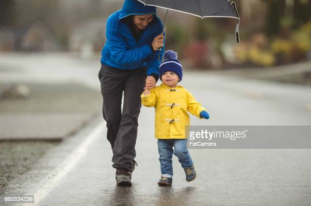 family walk in the rain - mother son shower stock photos and pictures