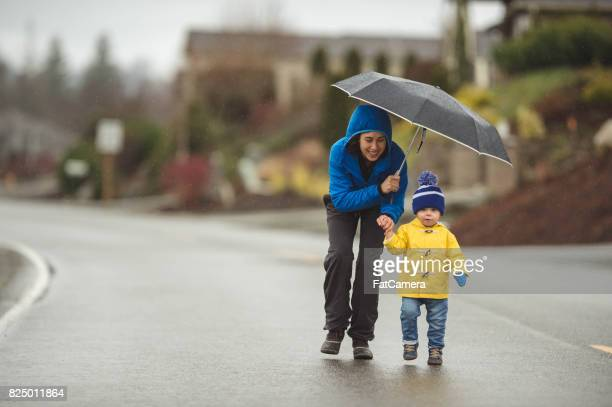 family walk in the rain - umbrella stock pictures, royalty-free photos & images