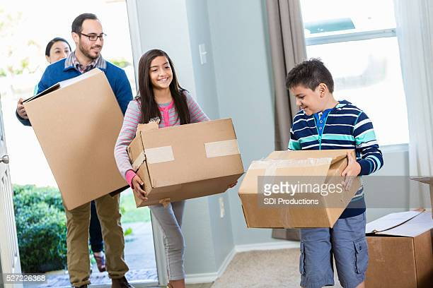 Family walk into their new home with boxes