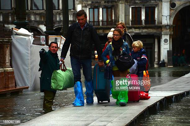 A family walk on bridge as they leave the flooded St Mark's square during acqua alta on November 1 2012 in Venice Floodwaters drenched Venice's St...