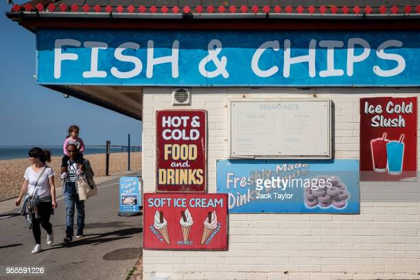 A family walk past a fish and chips kiosk during the warm weather on Bank Holiday Monday on May 7 2018 in Bognor Regis United Kingdom Britons across...