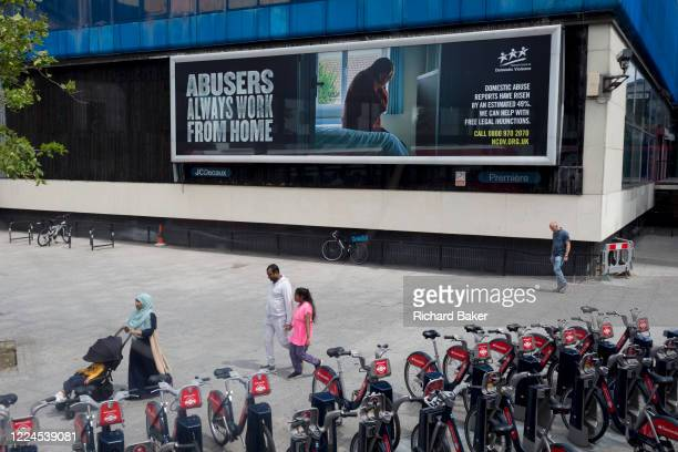 A family walk past a large billboard ad informing the public about domestic abuse during the Coronavirus pandemic lockdown which has seen a dramatic...