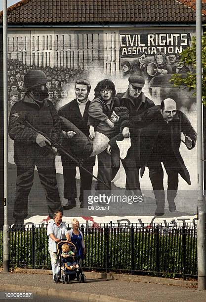 Family walk past a mural in the Bogside area of Londonderry close to where the Bloody Sunday killings took place in 1972 on June 15 2010 in...