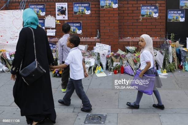 A family walk past bouquets of flowers left ouside the Finsbury Park Mosque in the Finsbury Park area of north London on June 20 following a van...