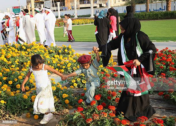 A family walk through flowers during a Dubai National Day parade on December 1 2008 in Dubai United Arab Emirates National Day festivities...