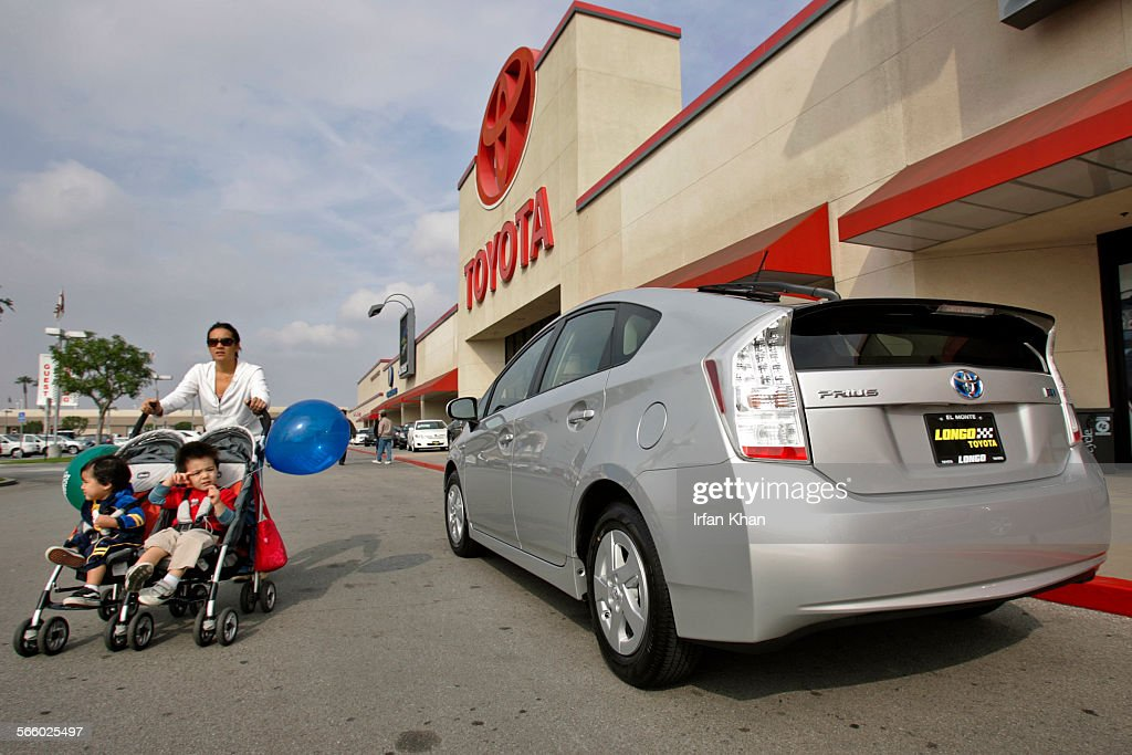 A Family Walk By A Toyota Prius Displayed At Longo Toyota Dealership In El  Monte