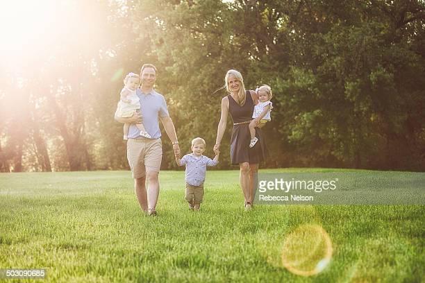family walking across grassy field