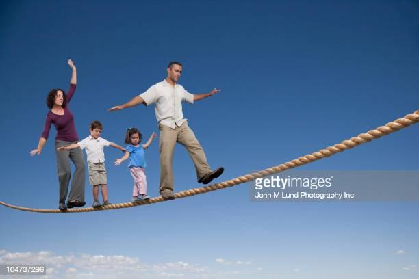 Family walking across tightrope