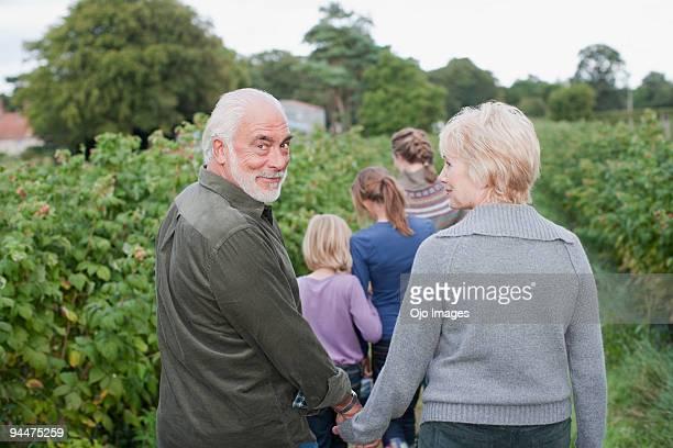 family walking along berry bushes - tourner photos et images de collection