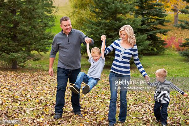 Family walking and holding hands in a park in autumn