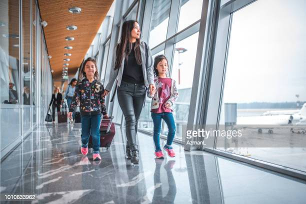 Family walking by window at airport terminal