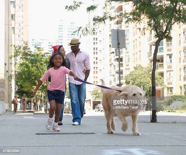 Family walking dog on urban sidewalk