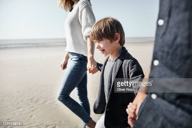 family walking hand in hand on the beach - two generation family stock pictures, royalty-free photos & images