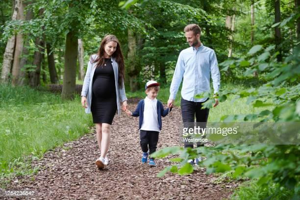 familie die hand in hand loopt - actieve levenswijze stockfoto's en -beelden