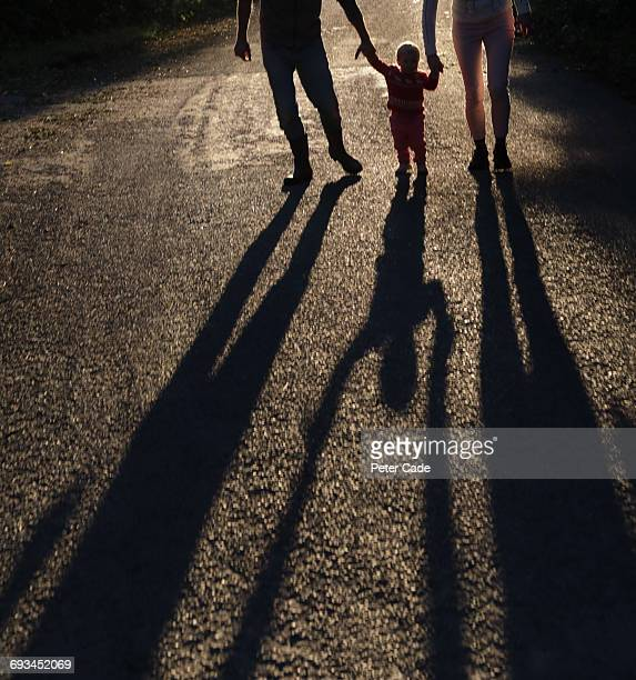 family walking holding hands, long shadows - family with one child stock pictures, royalty-free photos & images