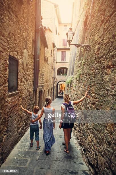Famille marchant dans la ruelle de Volterra, Toscane, Italie