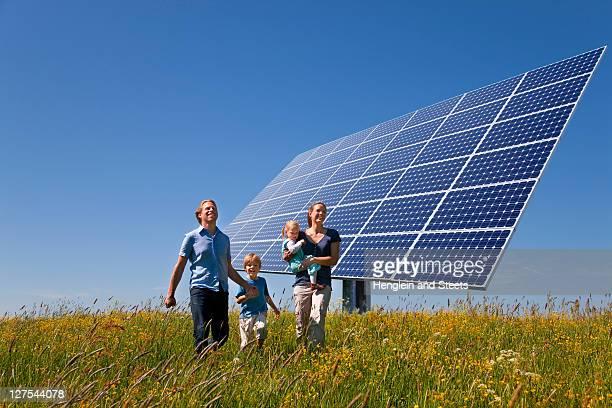 Family walking in field by solar panel