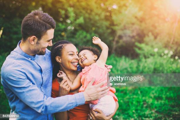 family walking in field carrying young baby girl - mixed race person stock pictures, royalty-free photos & images