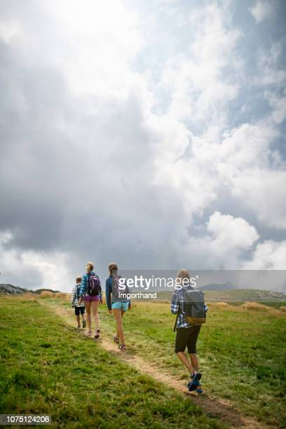 family walking in mountains monte baldo near lake garda, italy - veneto stock pictures, royalty-free photos & images