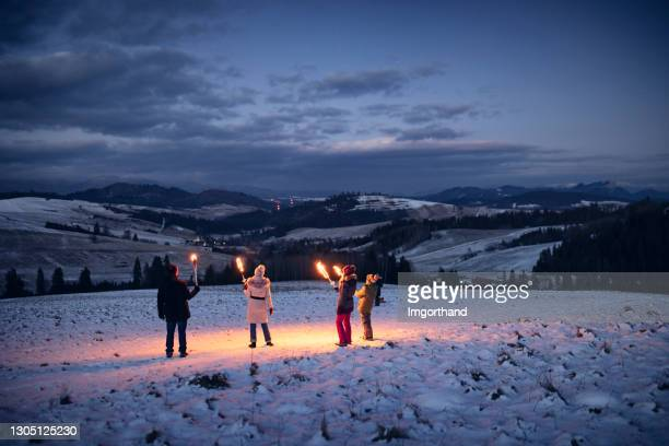 family walking in on hill with flaming torches - flame stock pictures, royalty-free photos & images