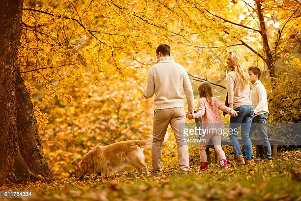 Family walking in park with their dog