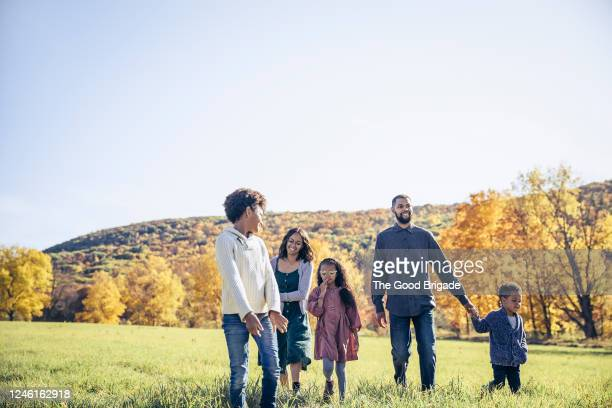 family walking in rural field in autumn - mixed race person stock pictures, royalty-free photos & images