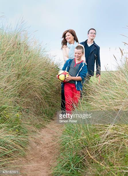 Family walking in sand dunes