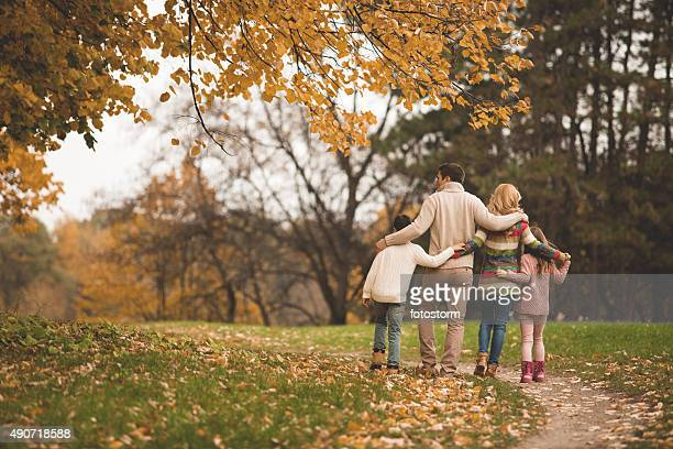 family walking in the park - autumn falls stock pictures, royalty-free photos & images