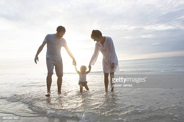 family walking in the sea in thailand
