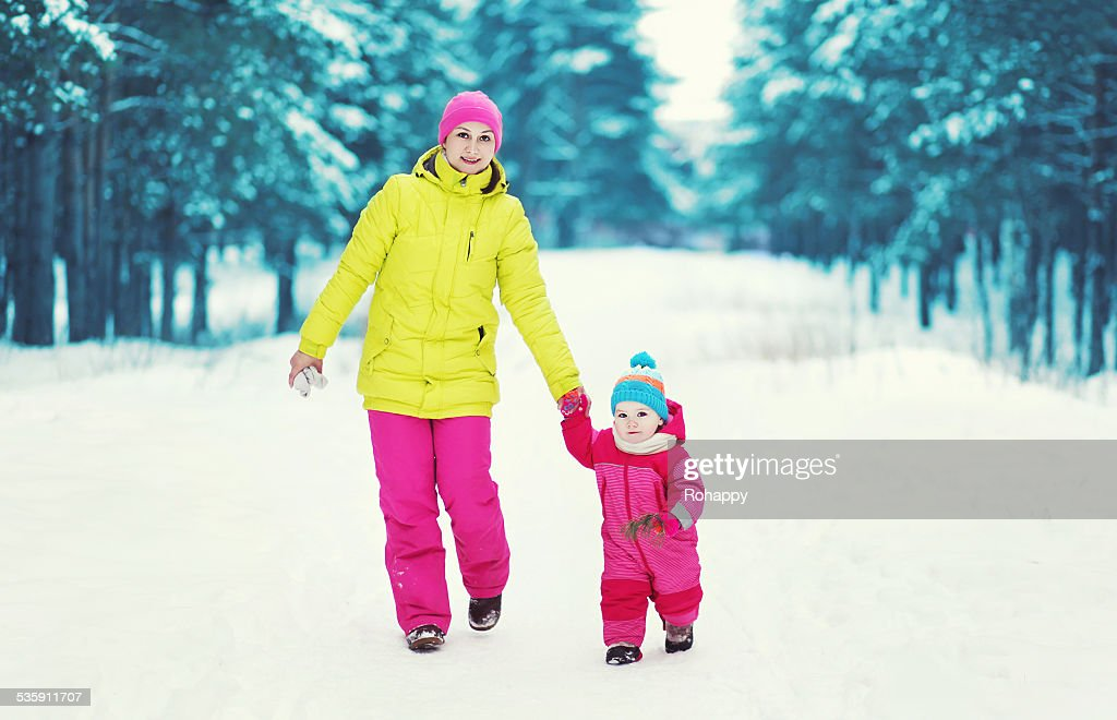 Family walking in the winter snowy forest : Stock Photo