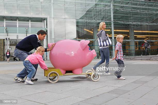 family walking in town with giant piggy bank