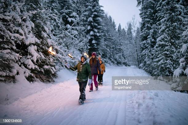 family walking in winter forest with torches - flame stock pictures, royalty-free photos & images