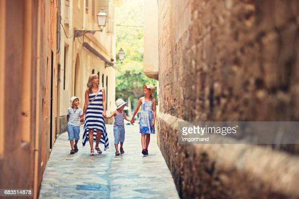 family walking narrow street of  palma de mallorca, spain - palma majorca stock photos and pictures