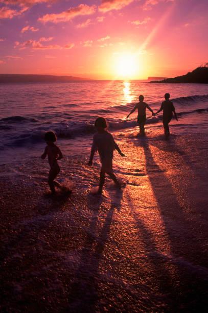 Family walking on beach at dusk, HI