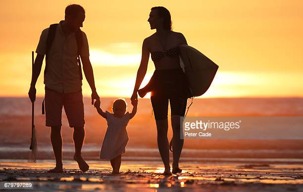 Family walking on beach at sunset