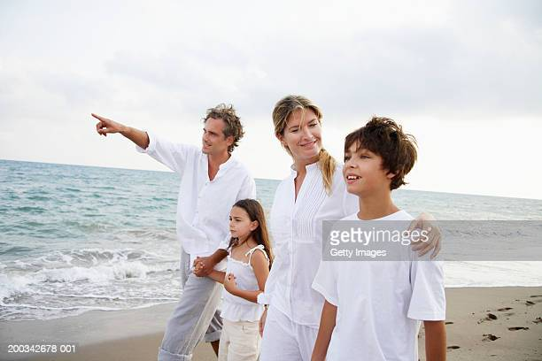Family walking on beach, father pointing, children (7-9)