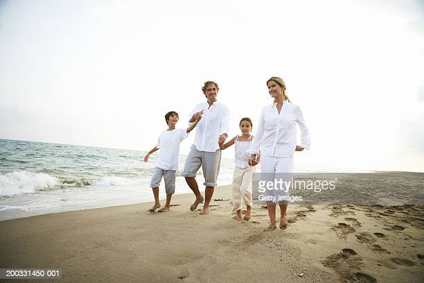Family walking on beach, holding hands
