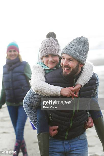 family walking on beach in winter - warm clothing stock pictures, royalty-free photos & images