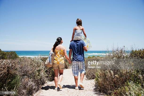 family walking on beach path toward ocean - woman carrying tote bag stock photos and pictures