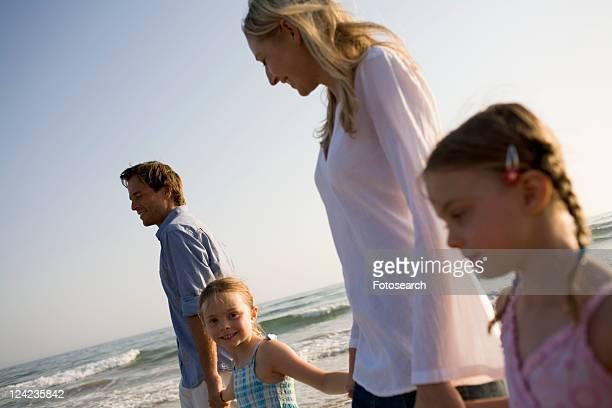 family walking on beach - 子供2人の家庭 ストックフォトと画像