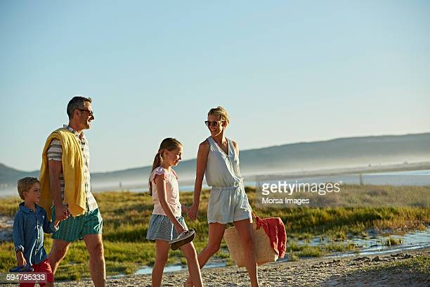 family walking on beach - blue shorts stock pictures, royalty-free photos & images