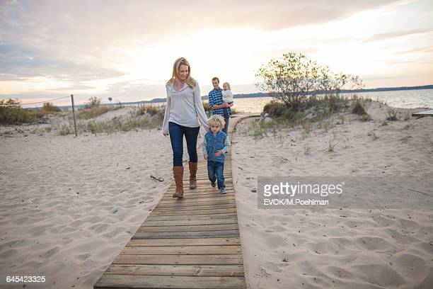 Family Walking on Boardwalk at Beach in Autumn