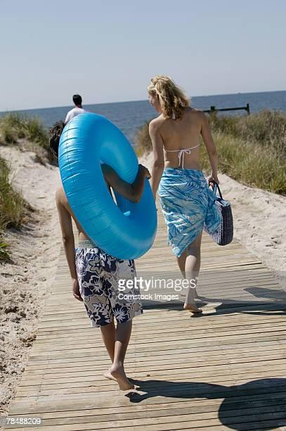 Family walking on boardwalk to the beach