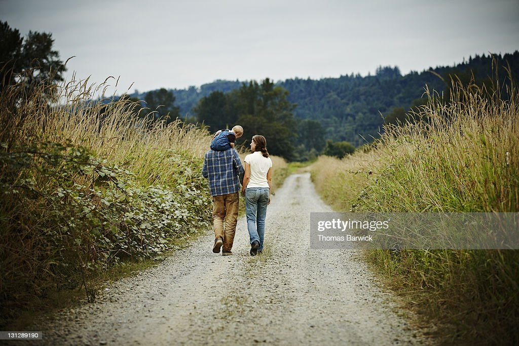 Family walking on dirt road rear view : Stock Photo