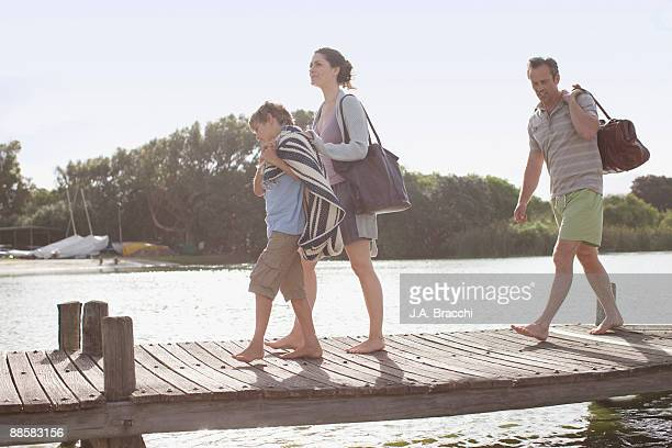 Family walking on dock near lake